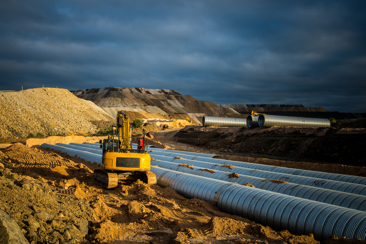 digger filling in culvert with steel pipes on mine